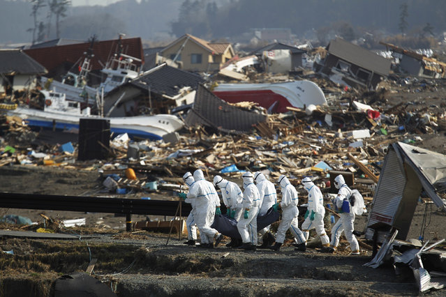 In this April 15, 2011 file photo,  Japanese police officers carry a body during a search and recovery operation for missing victims in the area devastated by the March 11 earthquake and tsunami in Namie, Fukushima Prefecture, northeastern Japan. (Photo by Hiro Komae/AP Photo)