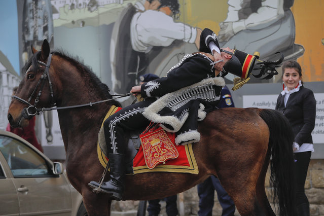An Ethnic Hungarian wearing a Hussar uniform leans back on his horse before a parade in Targu Secuiesc, Romania, Wednesday, March 15, 2017. Thousands of ethnic Hungarians paraded in Romania to celebrate the Hungarian national holiday, marking the anniversary of the 1848 revolution against the Habsburg empire. (Photo by Vadim Ghirda/AP Photo)