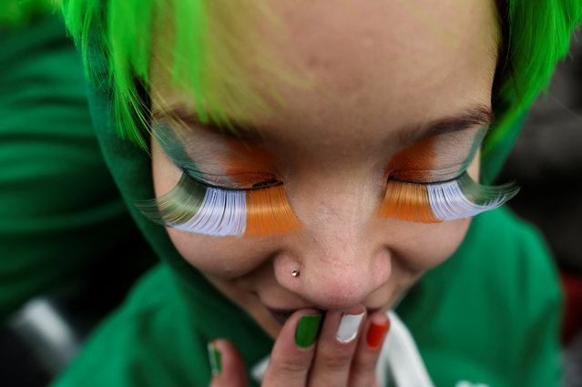 A woman watches the St. Patrick's day parade in Dublin, Ireland on March 17, 2017. (Photo by Clodagh Kilcoyne/Reuters)