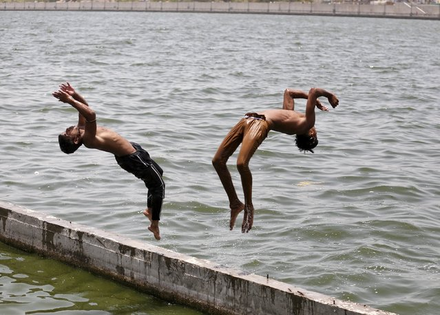 Boys jump into the waters of the Sabarmati river to cool off themselves on a hot summer day in Ahmedabad, India, May 24, 2015. (Photo by Amit Dave/Reuters)