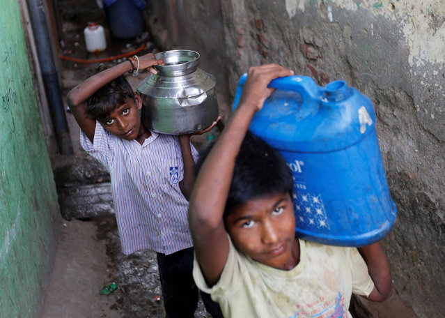 Boys carry containers filled with water from a communal tap at a slum in Mumbai, March 22, 2017. (Photo by Danish Siddiqui/Reuters)