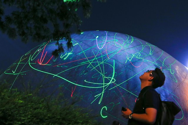 A man watches the dots of laser pointers move across the facade of the Hong Kong Space Museum during a flash mob staged to denounce the authorities' claim that laser pointers were offensive weapons in Hong Kong, China on August 7, 2019. Hundreds of Hong Kong protesters created their own light show to demonstrate against the arrest of a student detained for buying laser pointers, at the Space Museum in Tsim Sha Tsui. (Photo by Thomas Peter/Reuters)