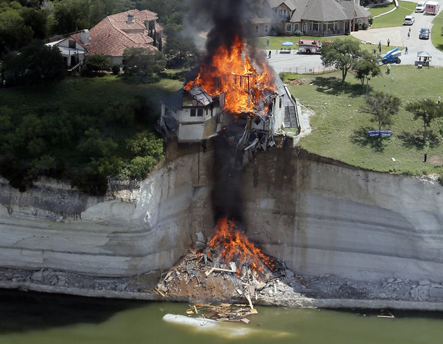 Smoke rises from a house deliberately set on fire, days after part of the ground it was resting on collapsed into Lake Whitney, Texas June 13, 2014. Building crews set fire to the luxury lake house left dangling about 75 feet on a decaying cliff that has been giving way underneath the structure. (Photo by Brandon Wade/Reuters)