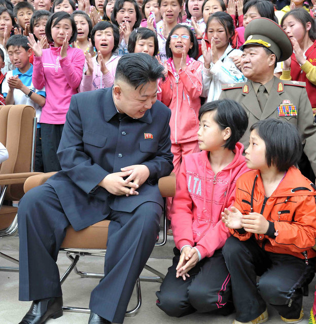 North Korean leader Kim Jong-un talks to children during a visit to the Pyongyang Myohyangsan Children's Camp situated at the foot of Mt. Myohyang in North Phyongan Province, in this photo released by North Korea's Korean Central News Agency (KCNA) on May 20, 2013. (Photo by Reuters/KCNA)