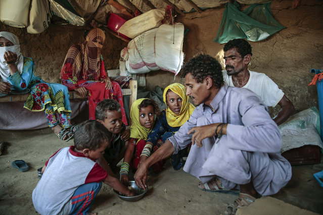 In this October 1, 2018, file photo, a man feeds children halas, a climbing vine of green leaves, in Aslam, Hajjah, Yemen. The U.N. food agency has begun a partial suspension of food aid to areas of Yemen controlled by the rebels amid accusations they were diverting aid from the war-torn country's hungriest people, the group said Thursday, June 20, 2019. (Photo by Hani Mohammed/AP Photo/File)