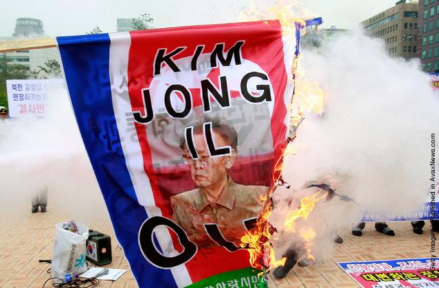South Korean protestors burn portraits of North Korean leader Kim Jong-Il and North Korean flag during a anti-North Korea rally at the National Assembly