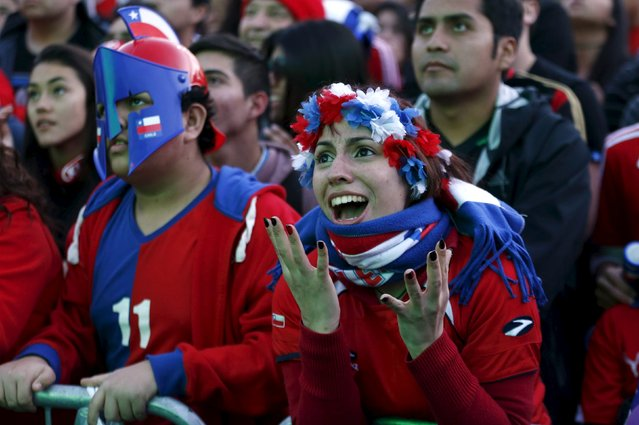 Chilean soccer fans watch the Copa America 2015 final soccer match between Chile and Argentina at a fan fest in Santiago, Chile, July 4, 2015. (Photo by Mariana Bazo/Reuters)