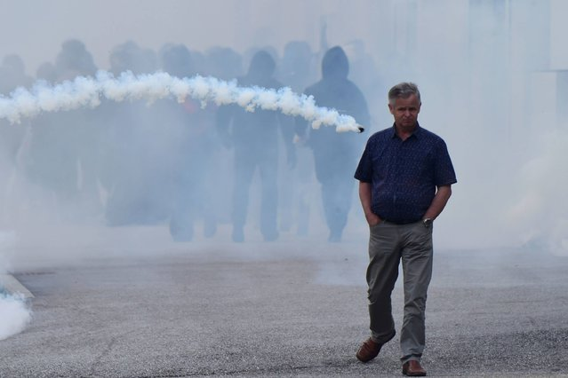 """A man walks along a street as a smoke bomb is thrown during clashes between """"No border"""" activists andItalian police at the Brenner train station on May 7, 2016 during demonstrations against Austria's possible decision to close the border with Italy. Vienna is threatening to resume checks on the Brenner Pass between the two countries as part of a package of anti-migrant measures if Italy does not do more to reduce the number of new arrivals heading to Austria. (Photo by Giuseppe Cacace/AFP Photo)"""
