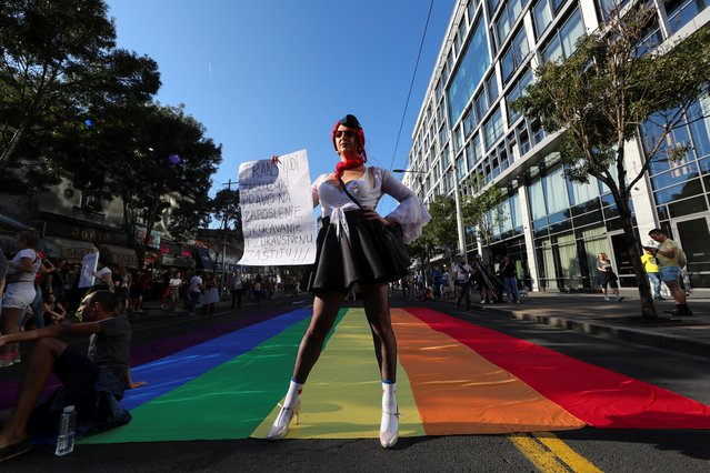"""A participant attends an annual LGBT pride parade in Belgrade, Serbia, September 15, 2019. The banner reads """"Transgender people deserve the right to work, home and health protection"""". (Photo by Marko Djurica/Reuters)"""