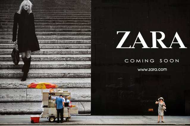 Dvir says the branding of the cityscape has become so ubiquitous, that the colorful, monumental advertisements, looming over the narrow streets, seem to be virtually unnoticed by the passersby. Giant billboards both dominate the urban landscape and blend into the background. Pictured here, a hotdog vendor looks at a woman next to a Zara billboard on 5th Avenue in New York, September 7, 2008. (Photo by Natan Dvir/Polaris)