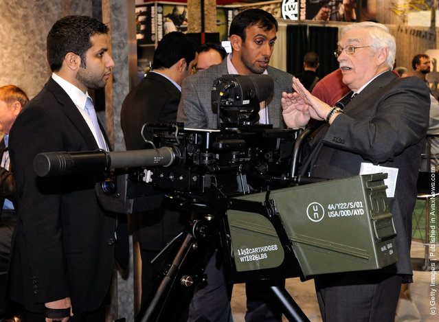 International Golden Group projects manager Saeed Aleghfeli from the United Arab Emirates and Matar Muhair Al Hamiri from the United Arab Emirates Armed Forces look on as Mike Costello with Rheinmetall Electro-Optics shows them a ballistic fire control computer attached to a belt-fed automatic 40mm HK GMG (grenade machine gun) at the Heckler & Koch booth