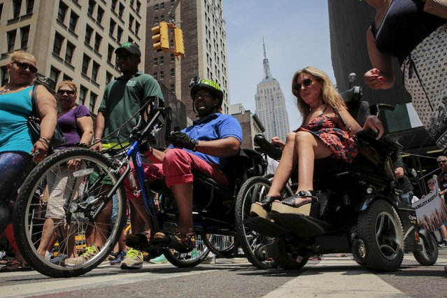 Quemuel Arroyo, (center L) policy analyst of New York City Department of Transportation and Danielle Sheypuk, (center R) licensed psychologist take part in the disability pride parade in New York, July 12, 2015. (Photo by Eduardo Munoz/Reuters)