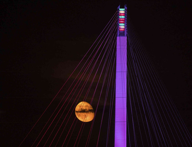 The moon rises over the Bob Kerrey Pedestrian Bridge in the early morning hours on Friday, June 21, 2019 in Omaha. Neb. (Photo by Chris Machian/Omaha World-Herald via AP Photo)