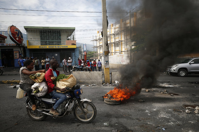 A motorcyclist drives past a burning barricade during a nationwide push to block streets and paralyze the country's economy as protesters press for President Jovenel Moise to give up power, in Port-au-Prince, Haiti, Monday, September 30, 2019. Opposition leaders and supporters say they are angry about public corruption, spiraling inflation and a dwindling supply of gasoline that has forced many gas stations in the capital to close as suppliers demand the cash-strapped government pay them more than $100 million owed. (Photo by Rebecca Blackwell/AP Photo)