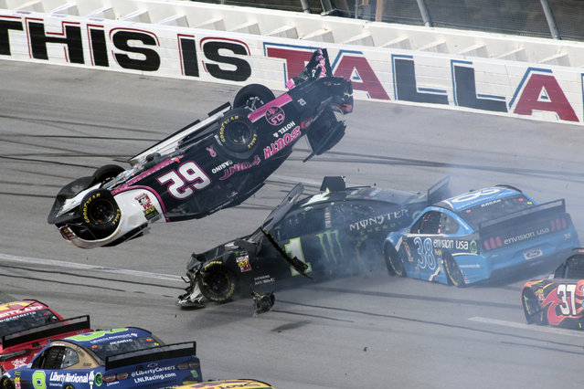 Brendan Gaughan (62) flips in Turn 3 as driver Kurt Busch (1) and David Ragan (38) pass underneath during a NASCAR Cup Series auto race at Talladega Superspeedway, Monday, October 14, 2019, in Talladega, Ala. (Photo by Greg McWilliams/AP Photo)