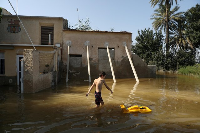 The youngest child in the Canizares family plays in the flooded vegetable garden of their summer home after torrential rains in Dolores near Alicante, Spain, September 16, 2019. (Photo by Susana Vera/Reuters)