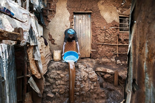 """""""The Last Illusion"""" in the title refers to, according to Grassani, the illusion of a favorable future for these migrants, who once in the city continue to suffer due to lack of resources, education and opportunities. Pictured in this photo, Rose, 34, works outside her mud hut in Nairobi, Kenya. Rose is from the Amagoru village in the Turkana province, an area that has suffered from an immense drought. (Photo by Alessandro Grassani)"""