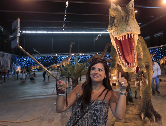 A woman takes a selfie during a dinosaur-themed exhibition in Beirut, Lebanon, July 11, 2015. (Photo by Jamal Saidi/Reuters)