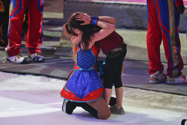 A performer hugs a young girl on the show floor after the final performance of the Ringling Bros. and Barnum & Bailey Circus, Sunday, May 21, 2017, in Uniondale, N.Y. (Photo by Julie Jacobson/AP Photo)