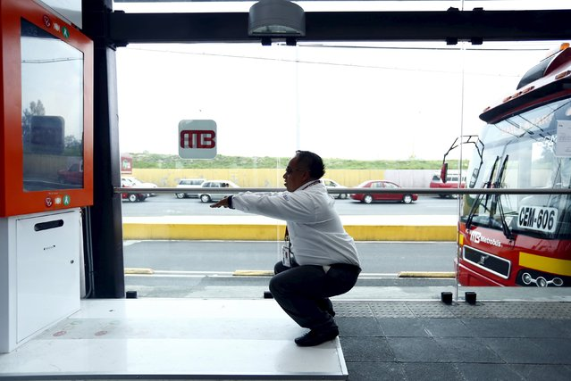 A metrobus driver performs squats at Rio de los Remedios metrobus station in Mexico City, July 23, 2015. To combat growing obesity, lawmakers have introduced a new campaign encouraging physical activity. This machine, installed in 21 metrobus stations around the city, asks its user to do 10 squats, and when all ten are performed correctly, it prints out a free ticket. (Photo by Edgard Garrido/Reuters)