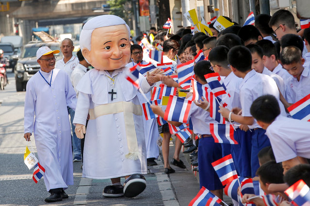 """A Thai man dressed in a Pope Francis costume greets young students waving Thai and Vatican flags Pope Francis' arrival to the Apostolic Nunciature Embassy of the Holy See in Bangkok, Thailand, 20 November 2019. Pope Francis has begun his three-day visit to Thailand, which runs from 20 to 23 November 2019. It will mark the 350th anniversary of the founding of the """"Mission de Siam"""" and is aimed at promoting inter-religious dialogue. Francis is the first pontiff to visit Thailand in nearly four decades. It will be the second papal to visit Thailand after the late John Paul II in 1984. (Photo by Diego Azubel/EPA/EFE)"""