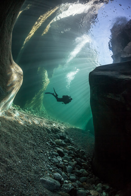 """""""Swiss Crystal River"""". Diver in crystal clear water of Verzasca river in Ticino – Switzerland. This dive site is dangerous if you don't respect the security rules. But it's a fabulous world with rounded rock. You can see across the surface from the bottom of the river. It's a kind of underwater cathedral. Photo location: Lavertezzo, Ticino, Switzerland. (Photo and caption by Marc Henauer/National Geographic Photo Contest)"""