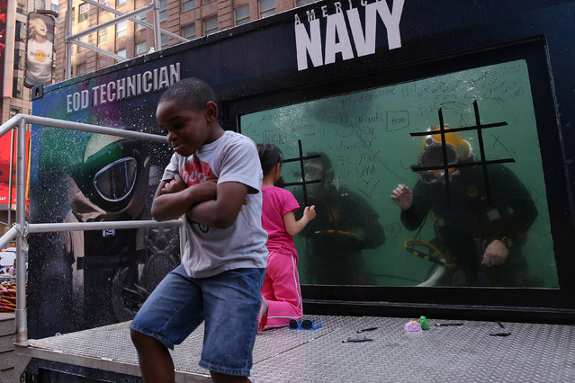 A child reacts to losing a game of tic-tac-toe he played on the glass of a dive tank used by the U. S. Navy Mobile Diving and Salvage Unit for promotion during Fleet Week in Times Square in the Manhattan borough of New York, U.S., May 27, 2016. (Photo by Carlo Allegri/Reuters)