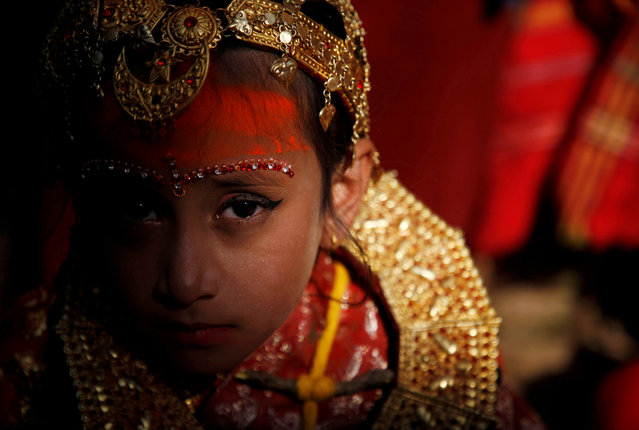 """Light illuminates a Newari girl as she takes part at the Ihi ceremony in Bhaktapur, Nepal on December 6, 2019. The two-day ceremony begins with purification rituals and ends with """"Kanyadan"""" (giving away the virgin) of the girl by her father. A Newari girl gets married thrice in her life, first with Bel, the fruit of a wood-apple tree, secondly with the sun, and lastly with her future husband. (Photo by Monika Deupala/Reuters)"""