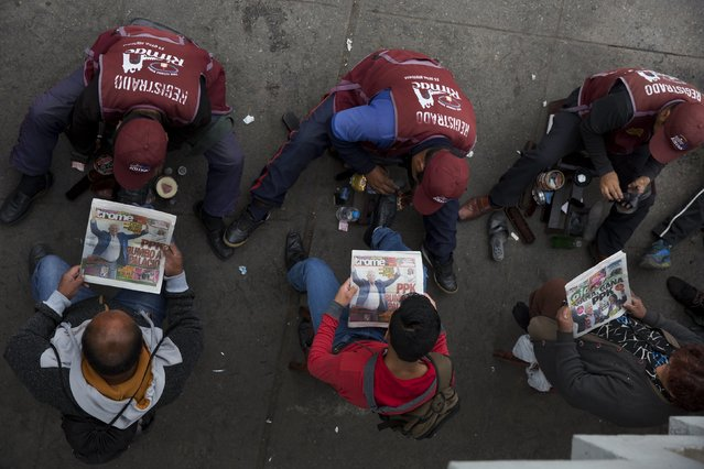 Clients have their shoes shined as they look at front page newspapers naming Pedro Pablo Kuczynski the winner of the country's runoff presidential election, in Lima, Peru, Monday, June 6, 2016. Early exit polls show Kuczynski with a slight lead over his rival Keiko Fujimori. (Photo by Rodrigo Abd/AP Photo)