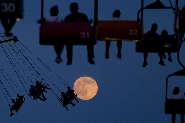 The moon rises as people sit on rides at the State Fair Meadowlands, Wednesday, July 1, 2015, in East Rutherford, N.J. The fair closes on Sunday. (Photo by Julio Cortez/AP Photo)