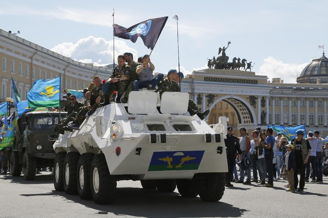 Former paratroopers ride an APC while celebrating Paratroopers' Day at Dvortsovaya (Palace) Square in St.Petersburg, Russia, Sunday, August 2, 2015. (Photo by Dmitry Lovetsky/AP Photo)