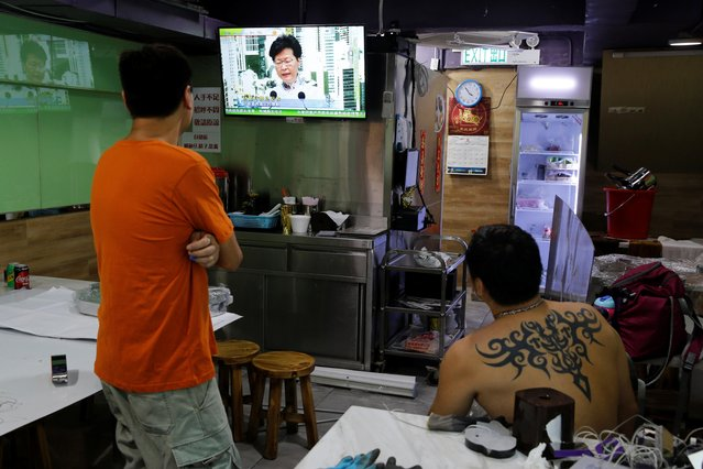 Men watch a TV broadcast of news conference of Hong Kong Chief Executive Carrie Lam inside a restaurant in Hong Kong, June 15, 2019. (Photo by Thomas Peter/Reuters)
