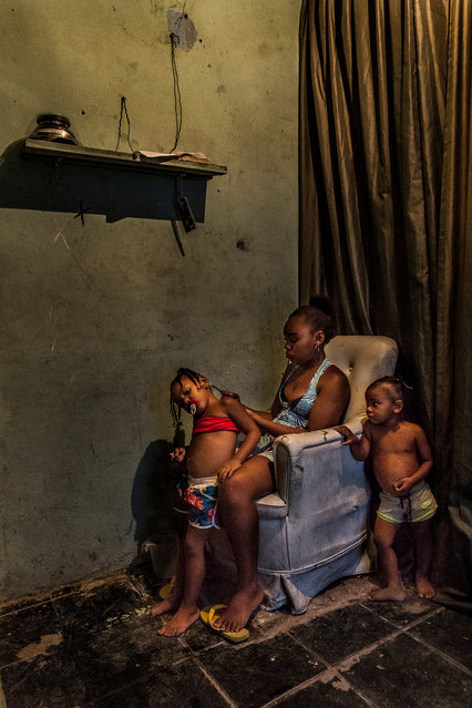 Inside one of the basic favela homes a mother braids her daughter's hair. Despite being marginalised and blamed for many of Rio's social problems, the favela's residents have created a society based on cooperation to survive in the crowded city. (Photo by Tariq Zaidi/The Guardian)