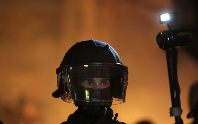 A masked police officer watches the situation when fire burn outside the Rote Flora squat during a protest against the G-20 summit in Hamburg, northern Germany, Thursday, July 6, 2017. (Photo by Markus Schreiber/AP Photo)