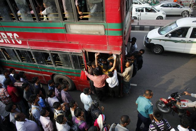 People wait to commute as an overloaded bus approaches on a street after office hours during Ramadan in Dhaka July 7, 2014. Although the government has shortened office hours during Ramadan, thousands of people are still unable to reach home before the time to break fast, due to heavy traffic, local media reported. (Photo by Andrew Biraj/Reuters)