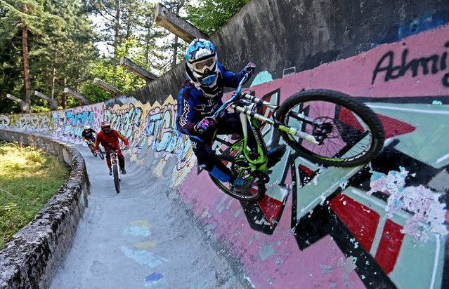 Downhill bikers Kemal Mulic (C), Tarik Hadzic (L) and Kamer Kolar train on the disused bobsled track from the 1984 Sarajevo Winter Olympics on Trebevic mountain near Sarajevo, Bosnia and Herzegovina, August 8, 2015. (Photo by Dado Ruvic/Reuters)