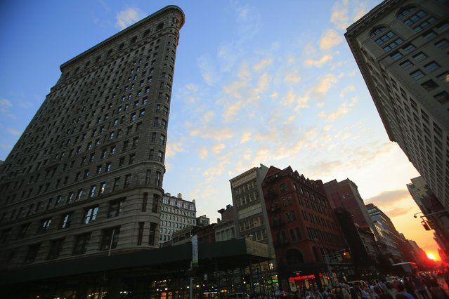 """The Flatiron Building (L) is seen at sunset during the bi-annual occurrence """"Manhattanhenge"""" in New York July 11, 2014. Manhattanhenge, coined by astrophysicist Neil deGrasse Tyson, occurs when the setting sun aligns itself with the east-west grid of streets in Manhattan, allowing the sun to shine down all streets at the same time. (Photo by Eduardo Munoz/Reuters)"""
