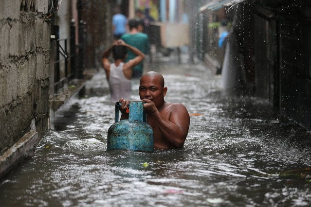 A resident carries a tank of liquified petroleum gas as he negotiates a flooded area while Typhoon Rammasun nears suburban Quezon city, Philippines on Wednesday, July 16, 2014. Typhoon Rammasun knocked out power in many areas but it spared the Philippine capital, Manila, and densely-populated northern provinces from being directly battered Wednesday when its fierce wind shifted slightly away, officials said. (Photo by Aaron Favila/AP Photo)