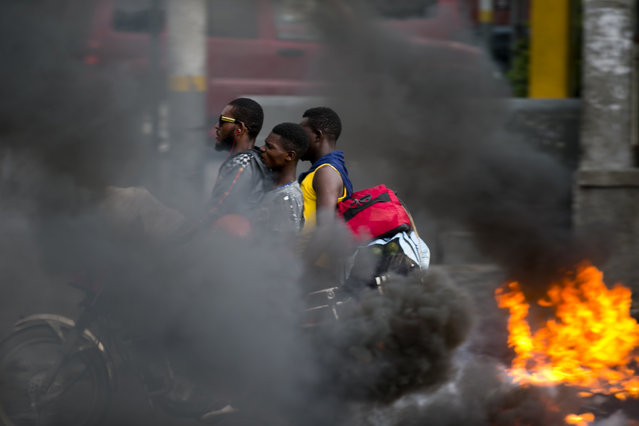 In this September 17, 2019 file photo, a moto-taxi driver takes two passengers past a burning barricade during a protest against fuel shortages in Port-au-Prince, Haiti. Haiti's economy, already fragile when the new round of protests began in mid-Sept., is in deep trouble with spiraling inflation and dwindling supplies, including fuel. (Photo by Dieu Nalio Chery/AP Photo)