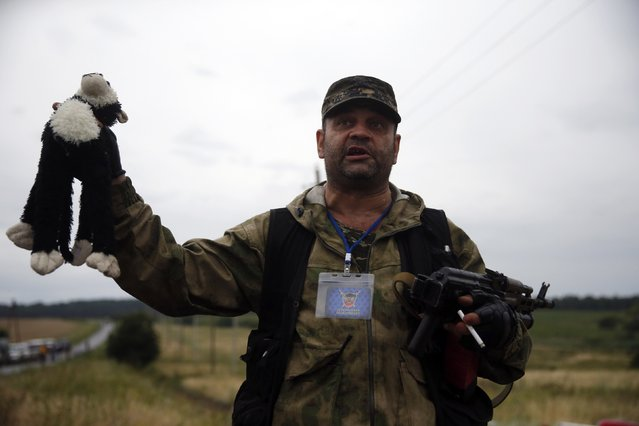 A pro-Russian separatist holds a stuffed toy found at the crash site of Malaysia Airlines flight MH17, near the settlement of Grabovo in the Donetsk region, July 18, 2014. As international investigators head to rebel-held eastern Ukraine to piece together what – and who – caused the Malaysian airliner to plunge into the steppe, securing evidence in the middle of a war zone is a major challenge. (Photo by Maxim Zmeyev/Reuters)