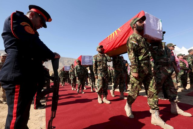 Kurdish peshmerga forces carry coffins, draped with Kurdish flags, containing the remains of Yazidis who were killed by militants of the Islamic State, during a burial ceremony at Mazar Sharaf al-Din, north of Sinjar Mountain, August 13, 2015. Remains of 68 Yazidis killed by militants of the Islamic State after the fall of their ancient homeland of Sinjar last year were buried in the Shrine of Mazar Sharaf al-Din, north of Sinjar Mountain. (Photo by Ari Jalal/Reuters)