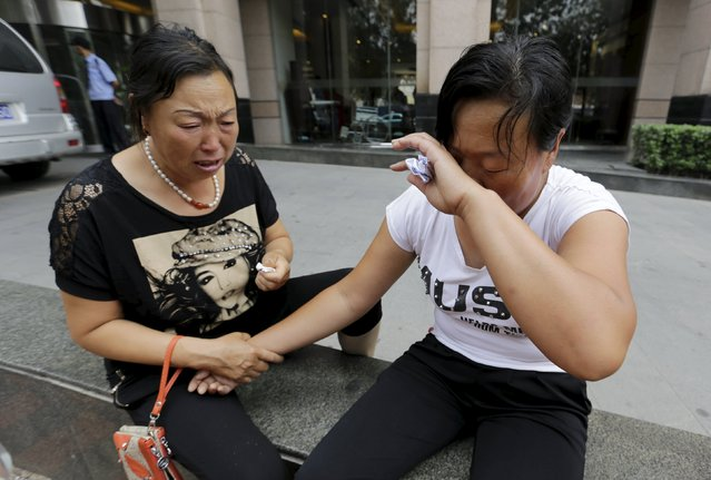 The mother (R) of missing firefighter Dong Zepeng wipes her face next to another family member as they cry outside the venue of a news conference after trying to demand for more information from government officials, following explosions on Wednesday night at Binhai new district in Tianjin, China, August 15, 2015. (Photo by Jason Lee/Reuters)