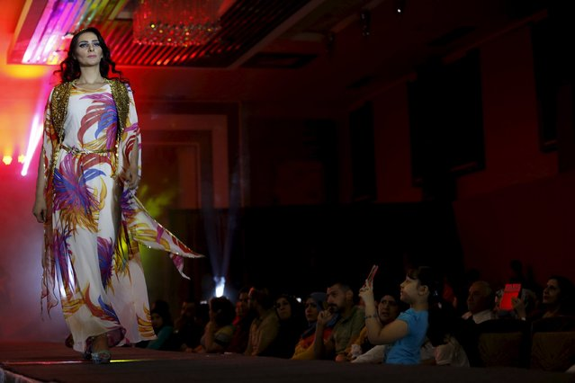 A girl in the audience takes a picture of a model presenting a creation by Iraqi designer Waffa Al-Shathar during a fashion show at the Hunting Club in Baghdad August 13, 2015. (Photo by Thaier al-Sudani/Reuters)