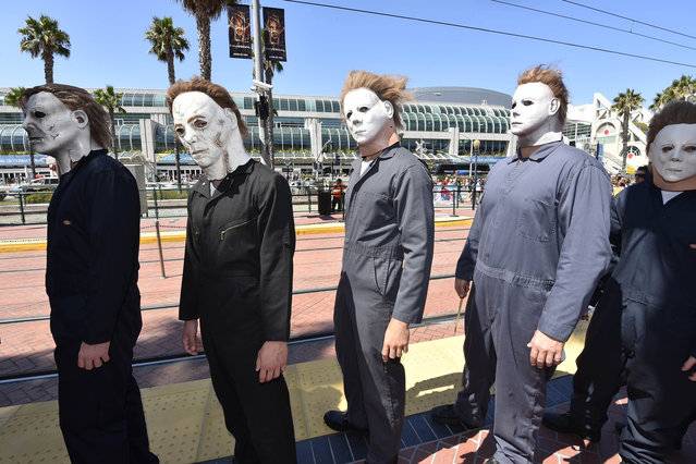 "People dressed as serial killers from movie ""Halloween"" wait at the trolley stop outside of the convention center on day 1 of the 2014 Comic-Con International Convention on Thursday, July 24, 2014 in San Diego. (Photo by Denis Poroy/Invision/AP Photo)"