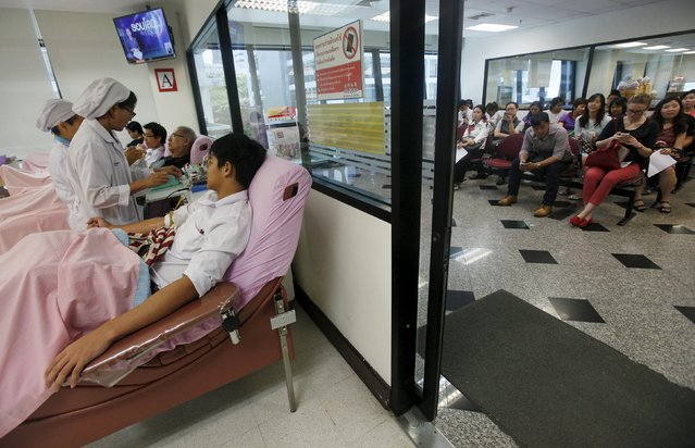 Volunteers (R) wait to donate blood at the Thai Red Cross National Blood Centre in Bangkok August 19, 2015. Some volunteers donating blood on Wednesday said they were doing it in response to Monday's deadly blast at Erawan shrine that killed at least 20 people. (Photo by Kerek Wongsa/Reuters)
