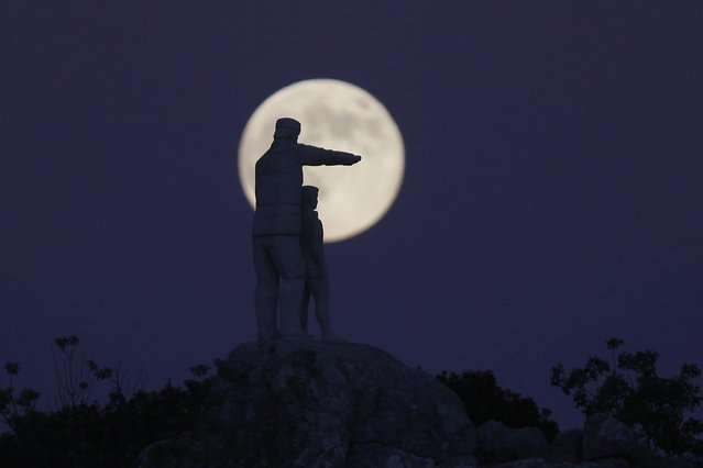 The statue of a man and a boy, a monument dedicated to forest rangers, is silhouetted against the supermoon as it rises at the Sierra de las Nieves (Mountain range of Snows) nature park and biosphere reserve between El Burgo and Ronda, near Malaga, southern Spain, August 10, 2014. Occurring when a full moon or new moon coincides with the closest approach the moon makes to the Earth, the supermoon results in a larger-than-usual appearance of the lunar disk. (Photo by Jon Nazca/Reuters)