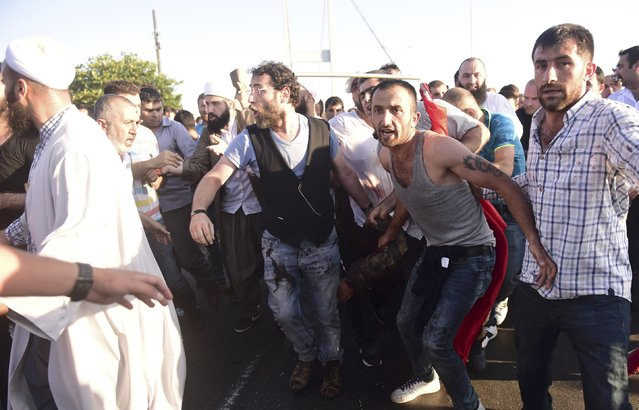 People drag a slodier after troops involved in the coup surrendered on the Bosphorus Bridge in Istanbul, Turkey July 16, 2016. (Photo by Yagiz Karahan/Reuters)