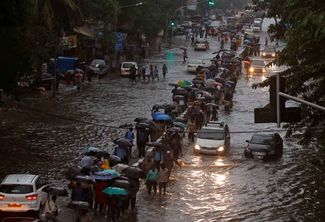 Commuters walk through water-logged roads after rains in Mumbai, August 29, 2017. (Photo by Shailesh Andrade/Reuters)