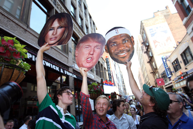 People hold Donald and Melania Trump Lebron James signs Monday, July 18, 2016, on E4th Street in Cleveland. Melania Trump is scheduled to address the convention, Monday. (Photo by Chad Rachman/The New York Post)