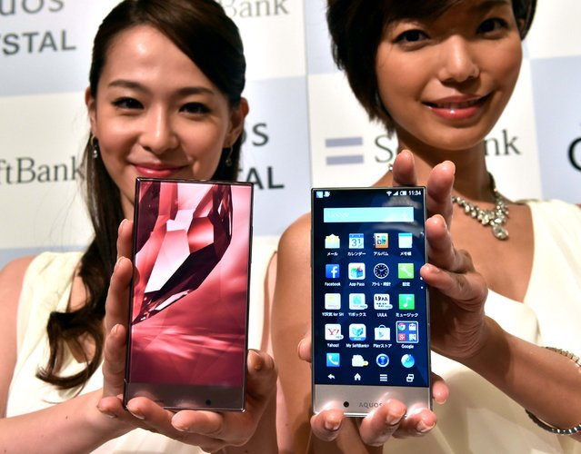 """Models display Japanese electronics giant Sharp's new smartphone """"Aquos Crystal"""" (R) and """"Aquos Christal X"""" (L), equipped with a 5.0-inch (R) and a 5.5-inch frameless LCD display with Harman Kardon's audio system in Tokyo on August 18, 2014.  Japanese mobile communication giant Softbank will start to sell Aquos Crystal in Japan's market from August 29, while Softbank's sibsidiary Sprint will launch in US market. (Photo by Yoshikazu Tsuno/AFP Photo)"""